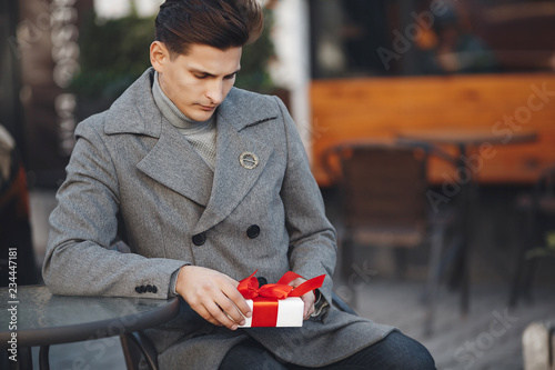 A Young Man In Gray Autumn Jacket With White Gift Box Tied