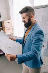 side view of smiling adult male architect in blue formal wear holding blueprint, using flip chart and working on project in office