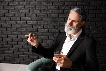 Senior man drinking whiskey and smoking cigar near dark brick wall