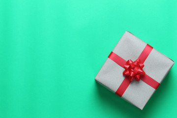 Brown Christmas gift box placed on a green art paper floor and have copy space.