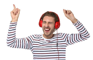 Young man listening to music on white background