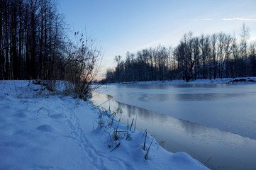Winter's river in ice and shore in the snow