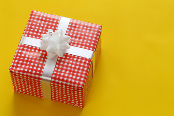 Red Christmas gift box placed on a yellow art paper floor and have copy space.