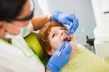 Dentist is examining teeth of a boy.