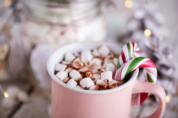 A close up of a pink mug full of cocoa with marshmallows on a wooden table