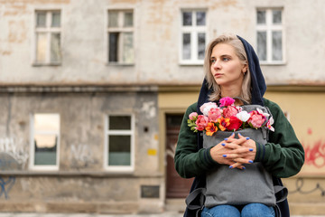 Blonde woman with backpack with bouquet of flowers is sitting, abandoned building on background.