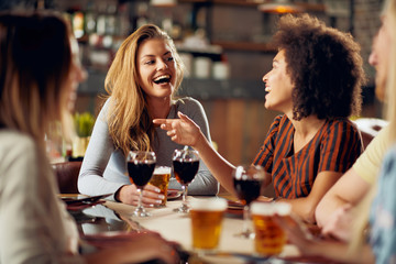 Multicultural friends sitting in restaurant and drinking wine and beer. Wall mural