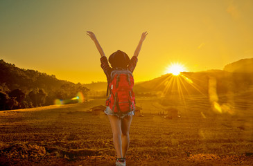 Beautiful woman with backpack happy on the hill at sunrise.