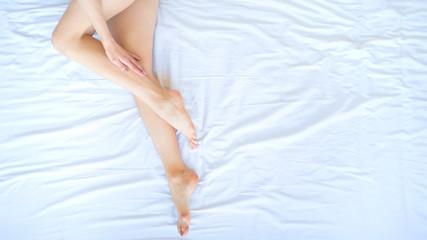 beautiful leg of a woman on white sheets