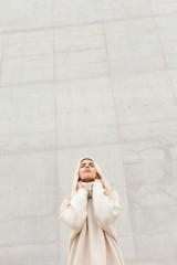 Elegant woman near white wall