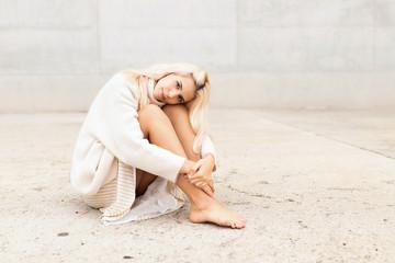 Elegant woman sitting near white wall