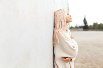 Sensual lady leaning on white wall