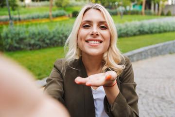 Image of charming woman 20s wearing jacket smiling and taking selfie photo, while walking through park