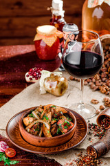 Fried potatoes slices in a brown plate and a glass of red wine on burlap on a dark wooden background. beautiful composition. Georgian cuisine. top view. close-up