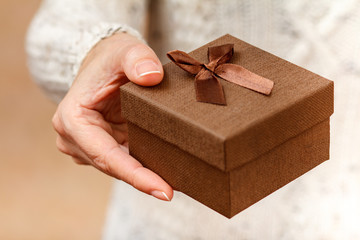 Woman holding a brown gift box in the hand.