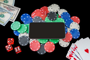 Mobile phone on poker chips with playing cards, dice and money