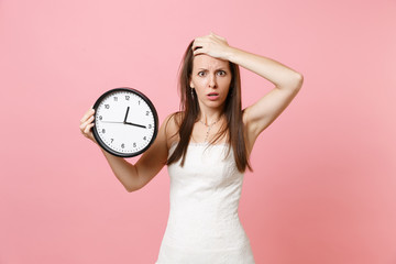 Portrait of worried bride woman in wedding dress clinging to head holding round alarm clock isolated on pastel pink background. Time is running out. Wedding to do list. Organization of celebration.