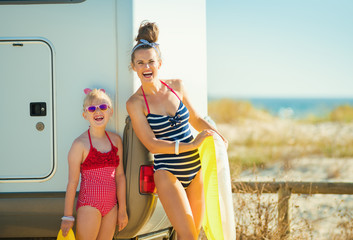 happy mother and daughter with yellow inflatable lifebuoy
