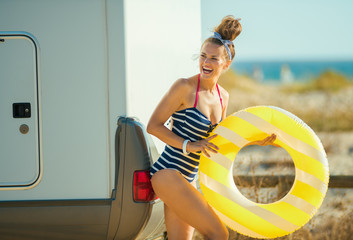 happy woman with yellow inflatable lifebuoy looking aside