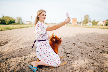 Nice looking beautiful blonde girl making selfie photo on smartphone. Young happy pretty female in stylish retro dress riding toy horse outdoor. Strange bizarre fashionable woman portrait.  Childhood.