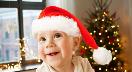 childhood, holidays and people concept - close up of happy little baby boy in santa hat over christmas tree lights background