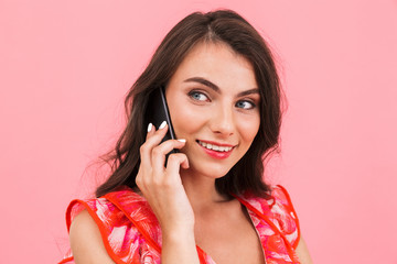 Woman posing isolated over pink background wall talking by mobile phone.