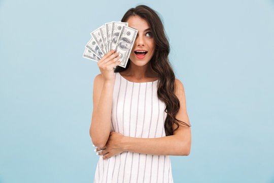 Beautiful young woman posing isolated over blue background wall holding money.