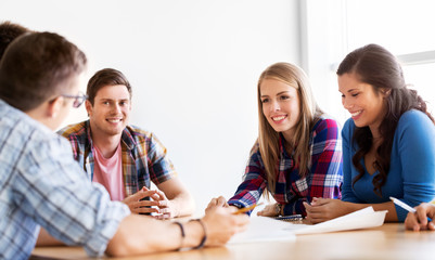 education, architecture and people concept - group of smiling students meeting at school