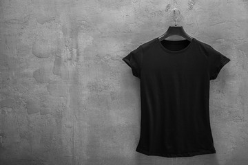 Front side of female black cotton t-shirt on a hanger and a concrete wall in the background. T-shirt without print and copyspace for your text on left side
