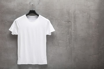 Front side of male white cotton t-shirt on a hanger and a concrete wall in the background. T-shirt without print and copyspace for your text on right side
