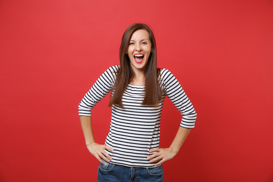 Joyful happy young woman in striped clothes keeping mouth wide open, standing with arms akimbo isolated on bright red wall background. People sincere emotions, lifestyle concept. Mock up copy space.