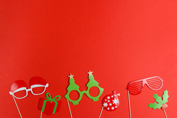 A Christmas party props for a photo booth on red background - funny glasses, ball, gift. Flat lay, copy space.