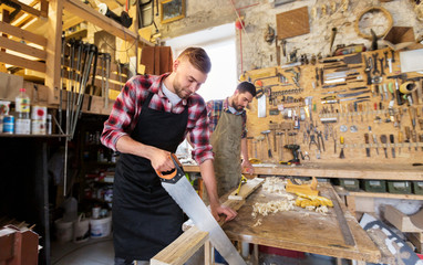 profession, carpentry, woodwork and people concept - two carpenters with saw and wood plank working at workshop