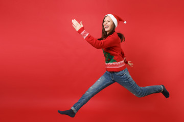 Laughing young Santa girl in knitted sweater, Christmas hat jumping, rising hands, spreading legs isolated on red background. Happy New Year 2019 celebration holiday party concept. Mock up copy space.