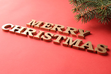 The inscription Merry Christmas and Christmas tree branches. gold letters on a red background. holidays. Christmas.