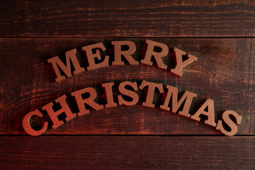 text merry christmas. gold letters on a brown wooden background. Top view of the new year. Christmas. holidays