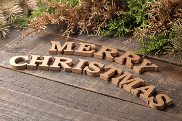 text merry christmas. golden letters and branches of a Christmas tree on a brown wooden background. new Year. Christmas. holidays