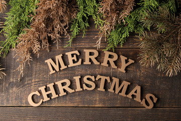 text merry christmas. golden letters and branches of a Christmas tree on a brown wooden background. View from above . new Year. Christmas. holidays