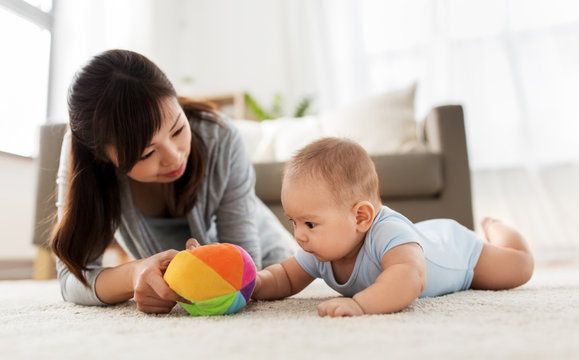 family and motherhood concept - happy mother and baby son playing with ball at home