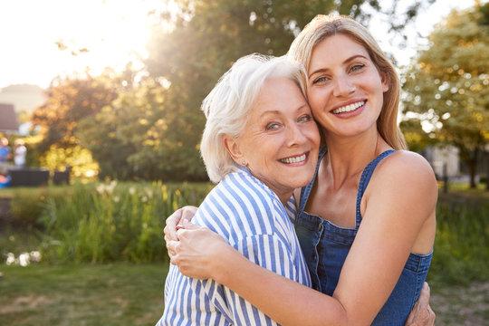 Portrait Of Smiling Mother Hugging Adult Daughter Outdoors In Summer Park