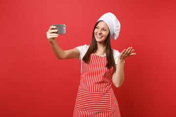 Housewife female chef cook or baker in striped apron, white t-shirt, toque chefs hat isolated on red wall background. Smiling fun woman doing selfie shot on mobile phone. Mock up copy space concept.