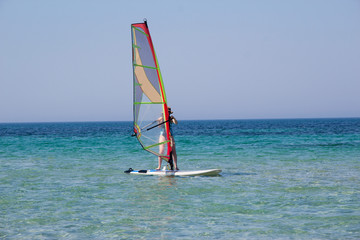 A woman windsurfing in the turquoise sea water in summer.