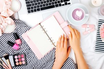 Fashion blogger working with laptop and planner  in bed, flat lay,  top view