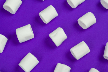 marshmallow laid out on violet paper background.