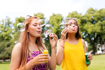 leisure and friendship concept - happy teenage girls or friends blowing bubbles at summer park