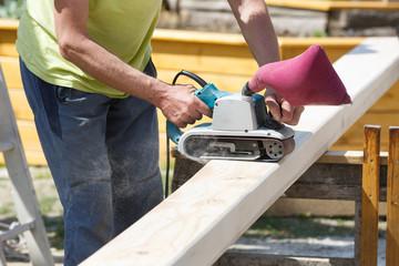 Carpenter softening edges on construction beams with beam sander