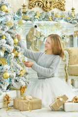 Happy girl decorating Christmas tree at home
