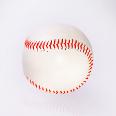 baseball ball with red firmware on the table with reflection