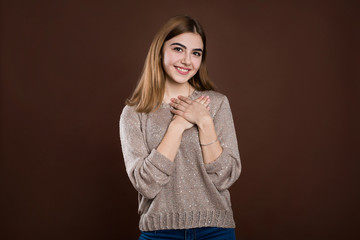 Happy beautiful female looks aside, wears warm sweater, dreams about date with handsome guy