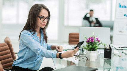 successful business woman with a smartphone in the workplace in the workplace in a modern office
